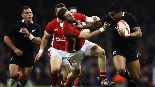 Julian Savea of the All Blacks fends off Wales' Alex Cuthbert