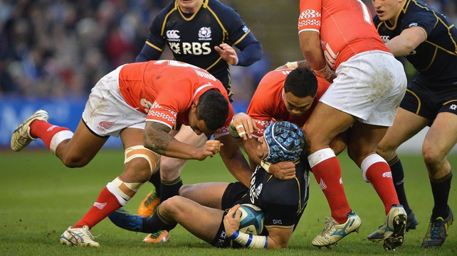 Scotland's Sean Lamont is tackled by Halani Aulika, Sione Piukala and Nili Latu of Tonga