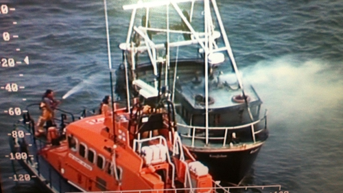 The Dunmore East Lifeboat attempts to extinguish the fire on the 'Kingfisher' (Pic: Irish Coastguard)