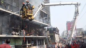 Bangladeshi firefighters use a water cannon on a crane to try to control the fire