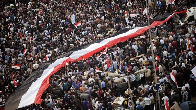 A giant Egyptian flag is passed through the crowd
