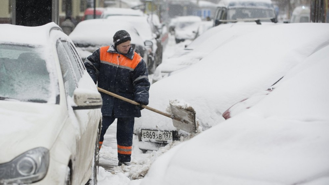 A municipal worker cleans snow on pavement between snow-covered cars in central Moscow