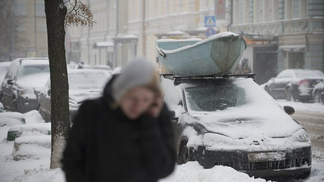 A woman walks past snow covered cars in central Moscow