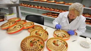 A woman puts the finishing touches to a traditional hand-made 'Anguila' (eel shaped) mazapan Christmas cake at the Santo Tome Obrador de Mazapan cake bakery in Toledo, Spain