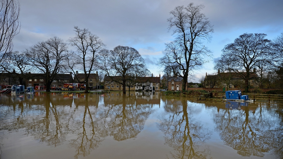 Trees are reflected in flood waters as residents begin to deal with the aftermath of the recent floods in Old Malton, England