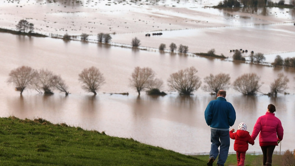 People walk from Glastonbury Tor as flood water in the fields below is seen in Somerset, England