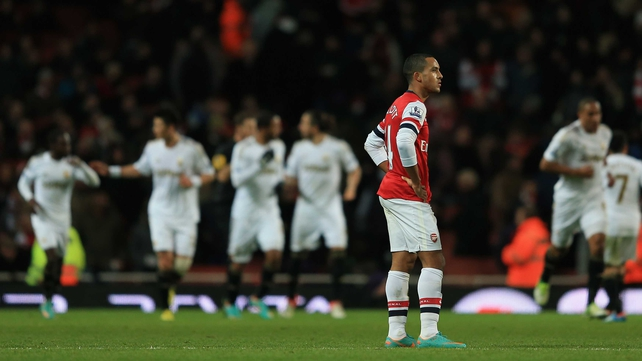 Theo Walcott turns away in disgust as the Swansea players celebrate Michu's first goal