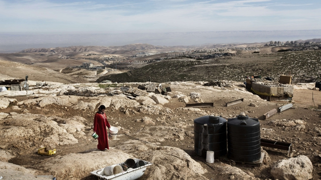 A Bedouin woman walks at her camp in the E1 area, between Jerusalem and the Israeli West Bank settlement of Maale Adumim