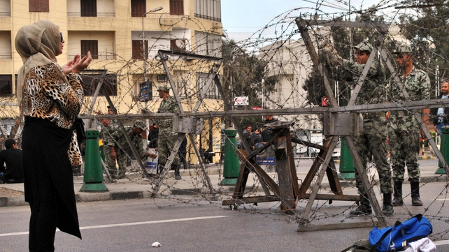 An Egyptian woman prays in front of Egyptian security as they lay out barbed wire along streets leading to the presidential palace