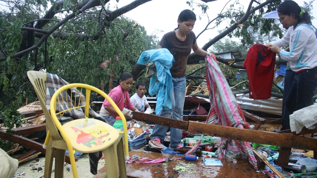 Residents gather their belongings after their house was destroyed by strong winds on the southern island of Mindanao