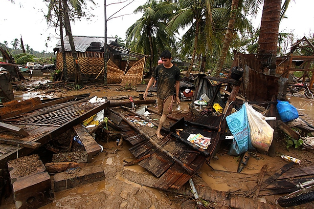 A man walks amongst destroyed houses after Typhoon Bopha hit Compostela town