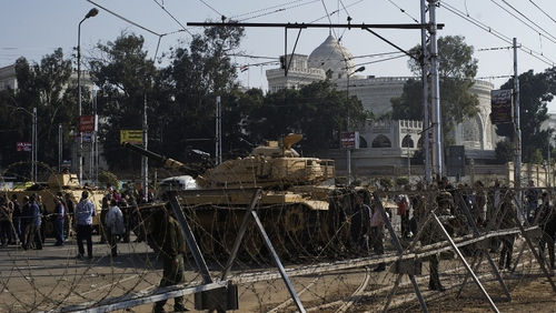 Egyptian army soldiers set up barbed wire barricades and deploy tanks outside the presidential palace