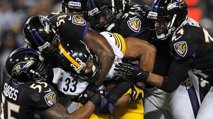 Running back Isaac Redman of the Pittsburgh Steelers is pulled down by a pack of Baltimore Ravens