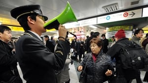 A station attendant uses a loudspeaker to explain the train service situations in Tokyo following the earthquake