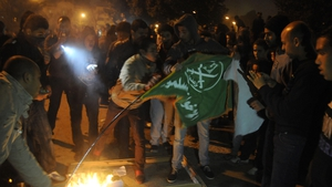 A flag is burned outside the Cairo headquarters of the Muslim Brotherhood after it was ransacked