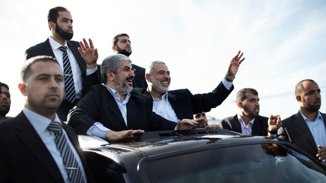 Hamas leader-in-exile Khaled Meshaal (C-L) and Hamas leader in Gaza Ismail Haniya (C-R) wave from the rooftop of a vehicle