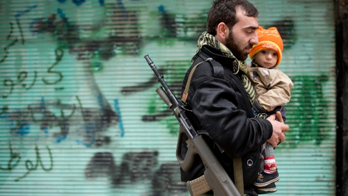 Rebel soldier in Aleppo carries his son to prayers