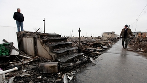 Dennis Kane (l) stands above the charred remains of his destroyed home in the hard hit Breezy Point neighbourhood of Queens in New York City