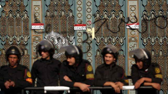 Riot policemen guard the presidential palace in Cairo
