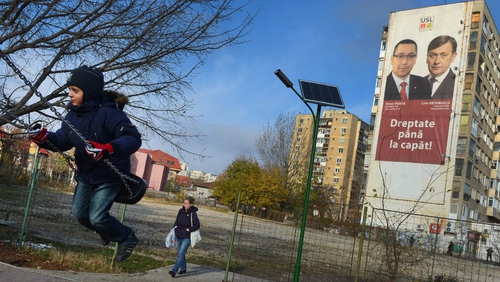 A girl surges on a swing as a poster of the Social Liberal Union (USL) party is displayed, Victor Ponta (l) and National Liberal Party leader Crin Antonescu (r) on a block of flats in Bucharest