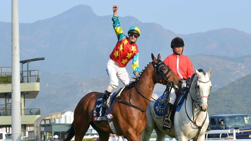 Zac Purton punches the air after steering Ambitious Dragon to victory in the Hong Kong Mile at Sha Tin