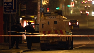 Police patrol the area in Belfast where a police officer was attacked with a petrol bomb