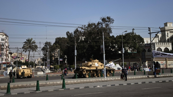 An Egyptian armoured personnel carrier and tank are deployed outside the presidential palace in Cairo