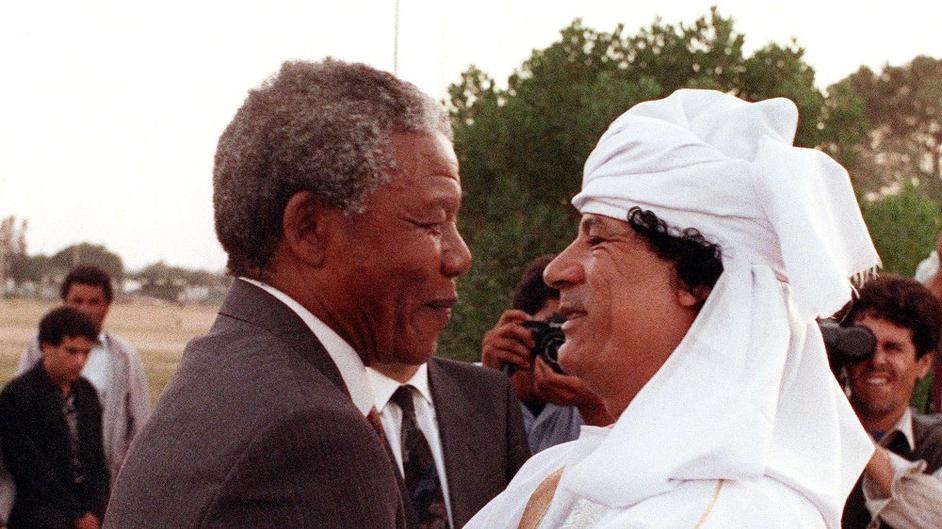 Nelson Mandela and Libyan leader Muammar Gaddafi hug on 18 May 1990, upon Mandela's arrival to Tripoli