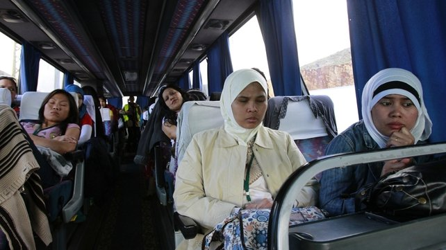 Asian women who were working in Syria are seen inside a bus leaving the war-torn country with the help of the International Organisation for Migration