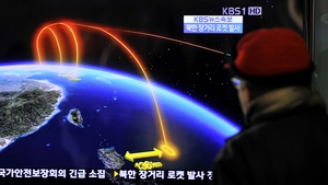 Travellers watch a TV screen broadcasting news of the launch in Seoul