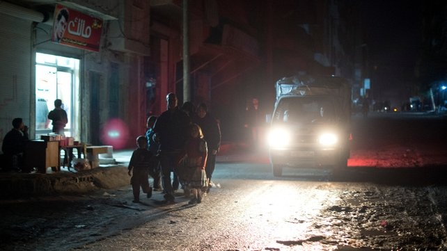 A Syrian family is silhouetted by a passing car as they walk along the main street of the Aleppo neighbourhood of al-Fardos