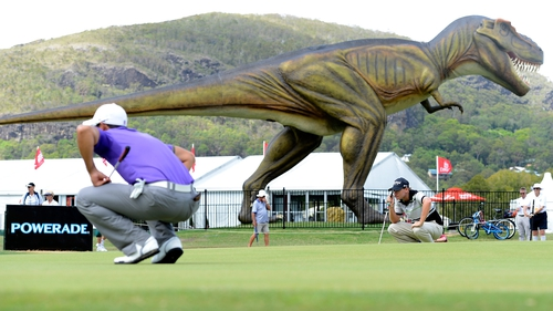 Matthew Stieger lines up a putt trying not to notice the giant model T-Rex dinosaur at the Palmer Coolum Resort