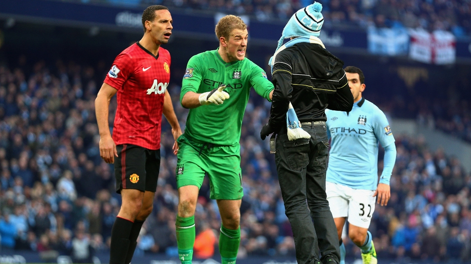 Joe Hart of Manchester City confronts a pitch invader during the Barclays Premier League match between Manchester City and Manchester United