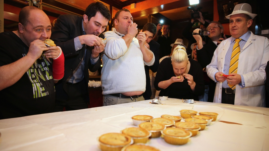 World Pie Eating Champion Martin Clare (centre) competes in the The World Pie Eating Championships at Harry's Bar in Wigan, England