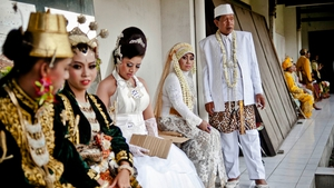 Brides and grooms prepare for a mass wedding ceremony in Yogyakarta, Japan