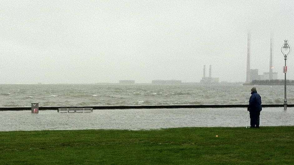 A man watches the sea at Clontarf at high tide