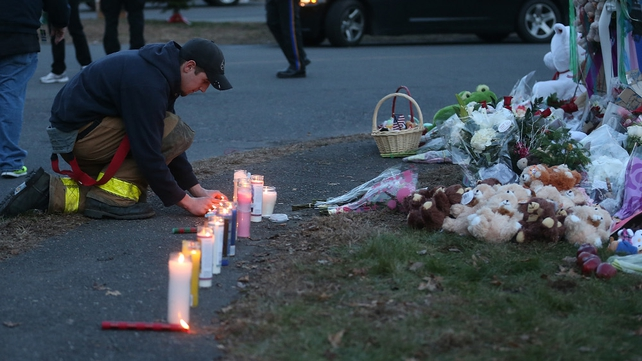 A firefighter kneels at a makeshift memorial near Sandy Hook Elementary School