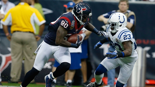 Andre Johnson of the Houston Texans runs the ball past Vontae Davis of the Indianapolis Colts