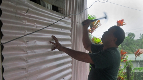 Local resident Aisea Latu nails a sheet of corrugated metal onto the shutters of his house on Laucala Bay Road, Suva