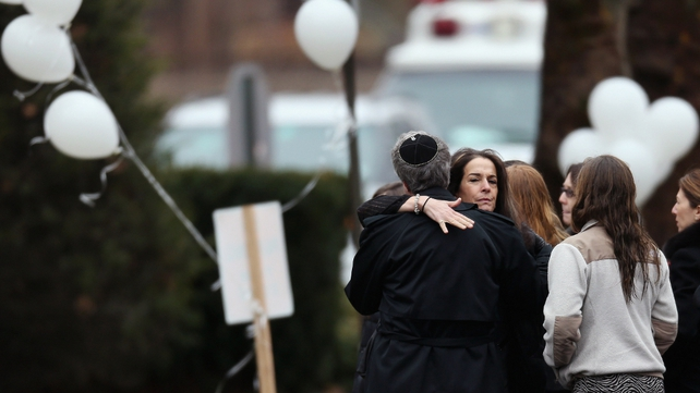 People embrace as they arrive for the funeral service of six year-old Noah Pozner