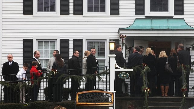 People wait outside before the funeral of six-year-old Jack Pinto
