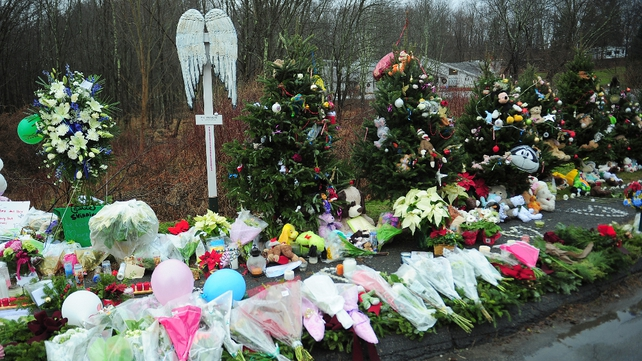 A line of Christmas trees form part of a makeshift shrine for the victims