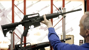 A customer at a gun show in Milwaukee examines a Bushmaster assault rifle similar to the one used in the Sandy Hook shootings