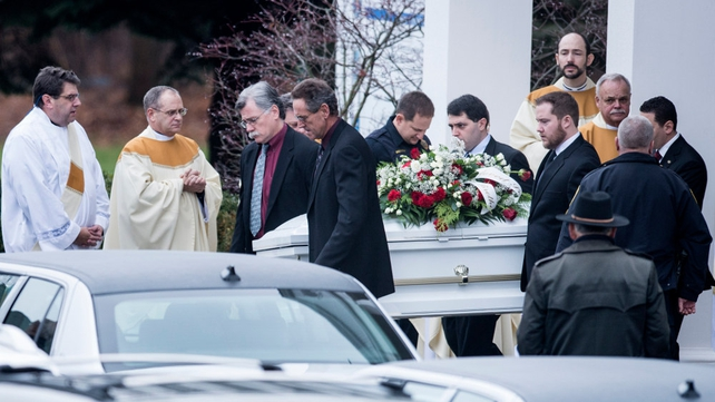 A casket with the body of James Mattioli is carried out of St Rose of Lima Roman Catholic Church