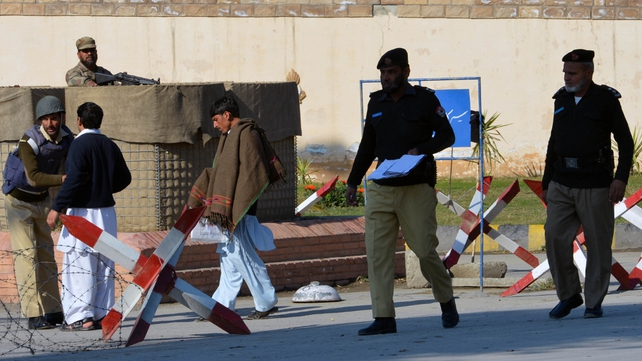 Pakistani policemen investigate a grenade attack site near the PAF Engineering Centre in Nowshera