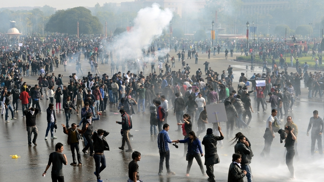 Demonstrators react as police use water cannon and tear gas during a protest