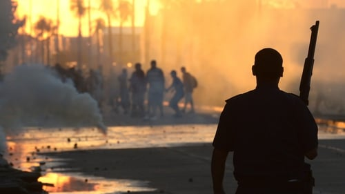 A policeman disperses looters after an attack on a supermarket in San Fernando in Buenos Aires province