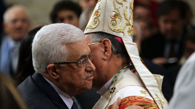 Foud Twal, the Latin Patriarch of the Holy Land, embraced Palestinian President Mahmoud Abbas (l) as the Palestinian Authority leader attended the Christmas midnight mass in Saint Catherine's Church in Bethlehem