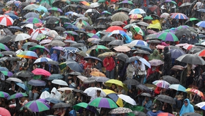 Tennis fans stay in their spots during a torrential downpour on the final day at Wimbledon in July