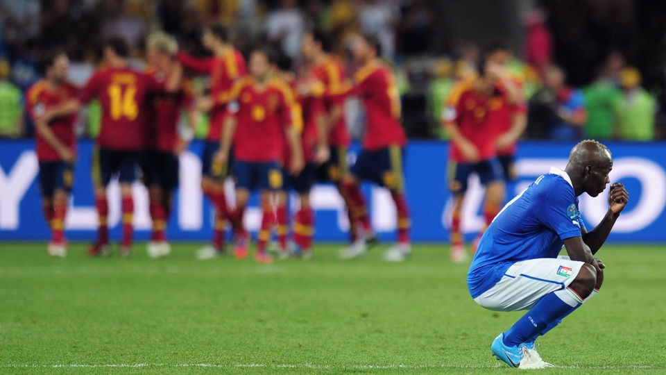 A dejected Mario Balotelli can't watch as Spain celebrate winning the Euro 2012 final against Italy